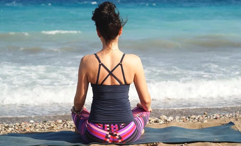 Méditer différemment avec une femme sur la plage